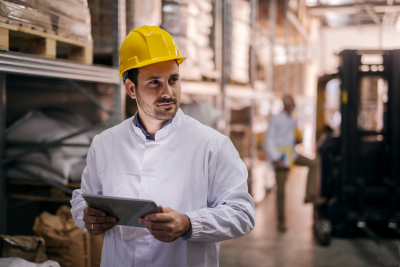 a manager standing in factory and holding tablet